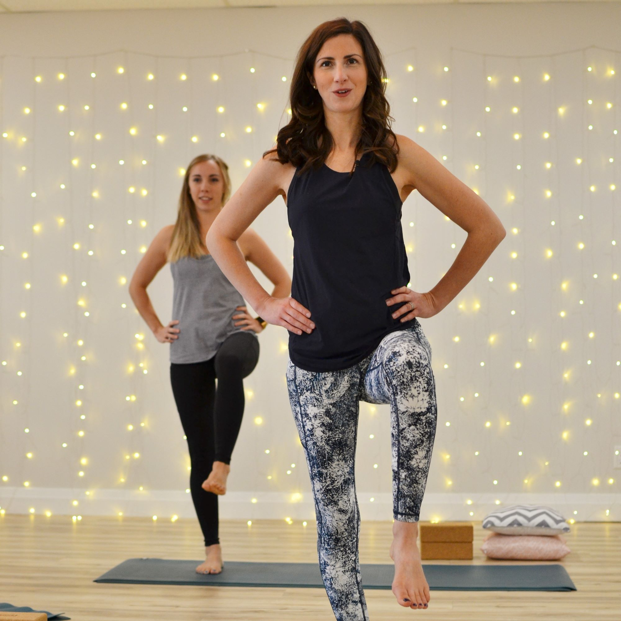 stephanie reynolds standing on yoga mat with hands on hips and one knee lifted