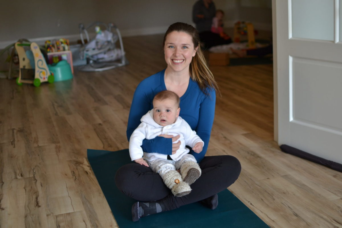 mom holding baby on a yoga mat